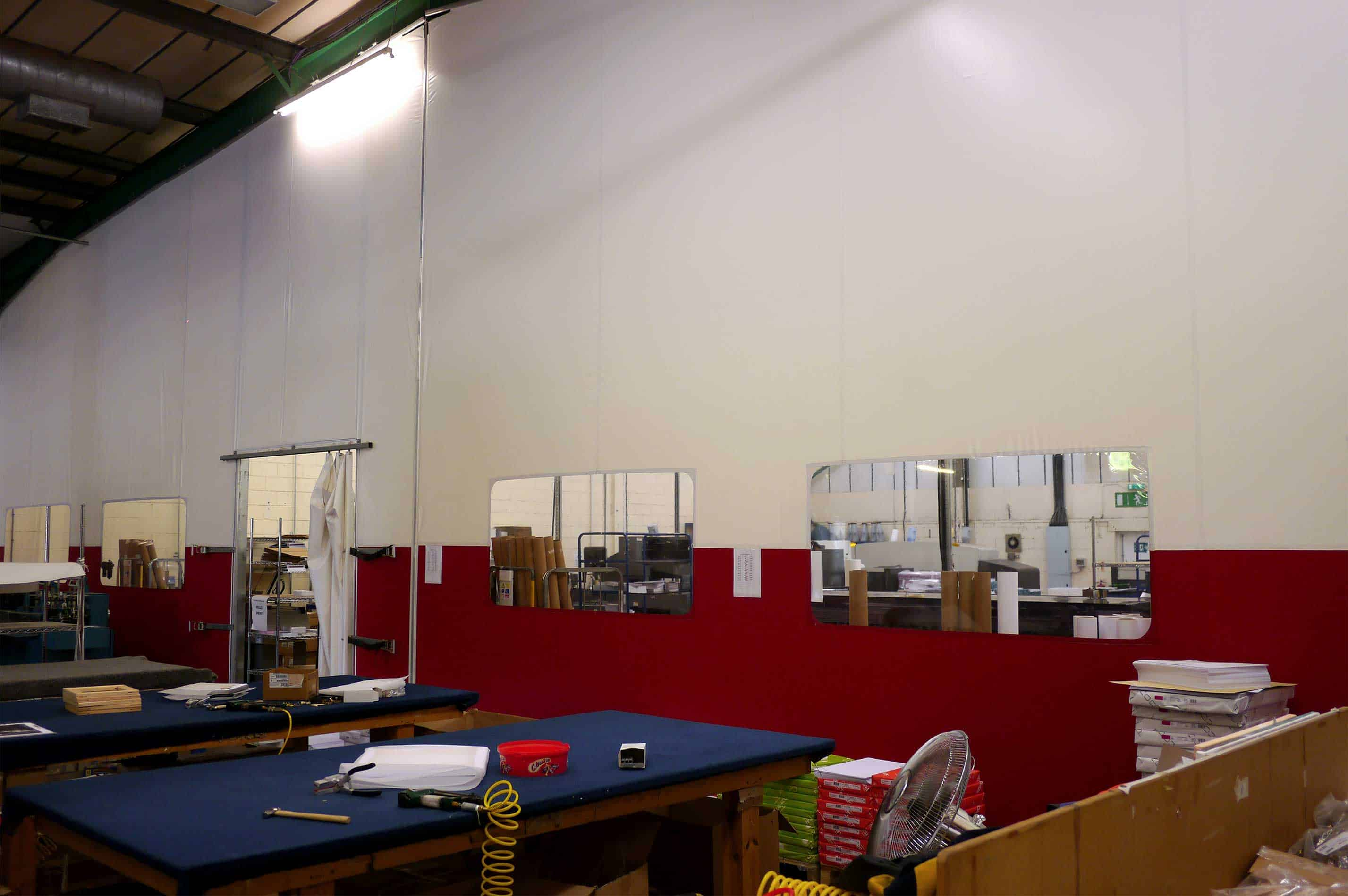 Flexible fabric partition with window cut-outs and personnel doors by McGregor Fabric Structures